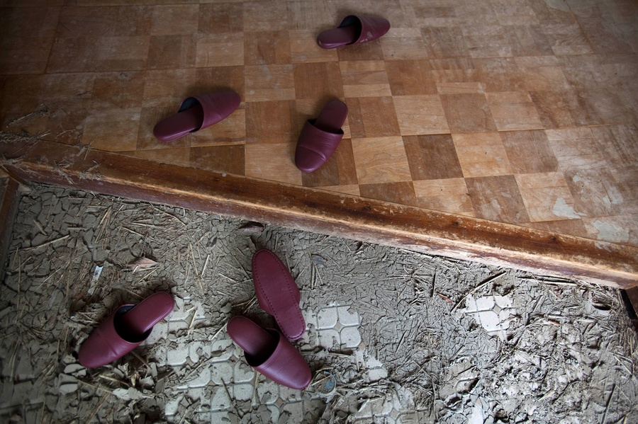 In April 8, 2011 photo, slippers are left in the entrance of a building in the Odaka area of Minamisoma, inside the deserted evacuation zone established for the 20 kilometer radius around the Fukushima Daiichi nuclear reactors