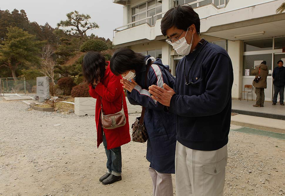 People outside the junior high school, where a makeshift morgue has been set up, pay their respects to those who died in the earthquake and tsunami