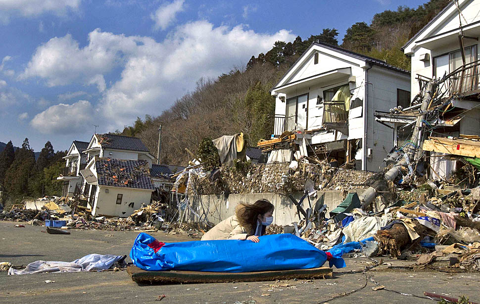 Onagawa, Japan — Tayo Kitamura, 40, kneels in the street with the wrapped body of her mother, Kuniko, 69, after Japanese firemen discovered the body inside the ruins of her home in northeastern Japan