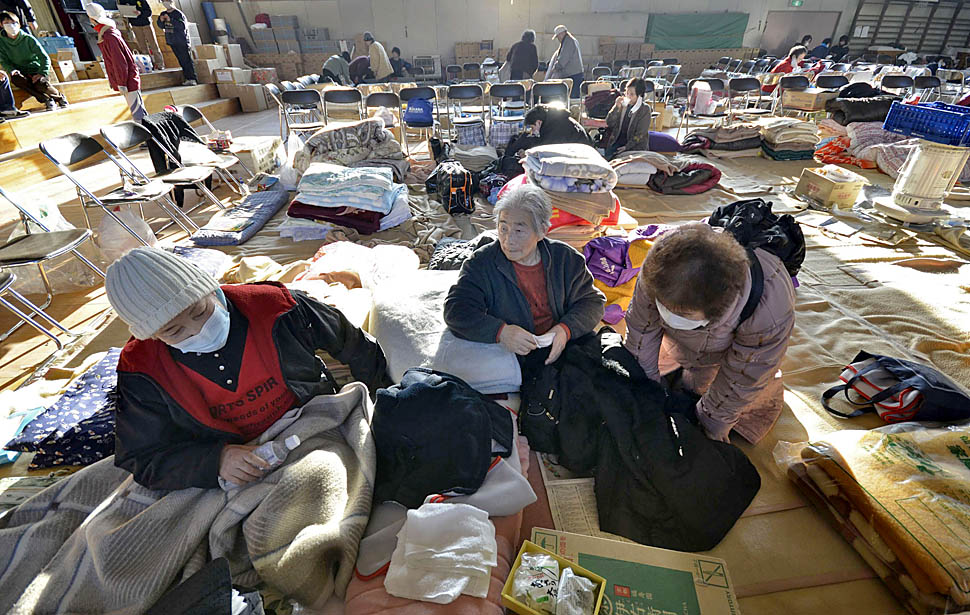 Refugees rest in a school gym being used as a shelter after their houses were destroyed by last week's earthquake and tsunami