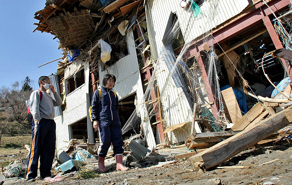 Survivors walk amid devastation in  Minamisanriku Town in Miyagi prefecture