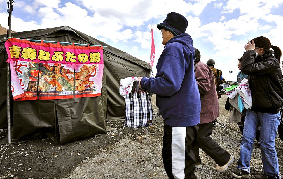 A group of women head for a makeshift hot bath set up by Japan's Self-Defense Forces personel in the tsunami-stricken city of Kamaishi