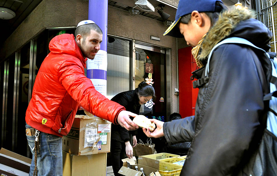 Somech Roy, left, an Israeli living in Sendai, gives bread to a man in downtown Sendai. A friend baked 15,000 loaves of bread for free distribution after he received donations from Jews in Japan and abroad