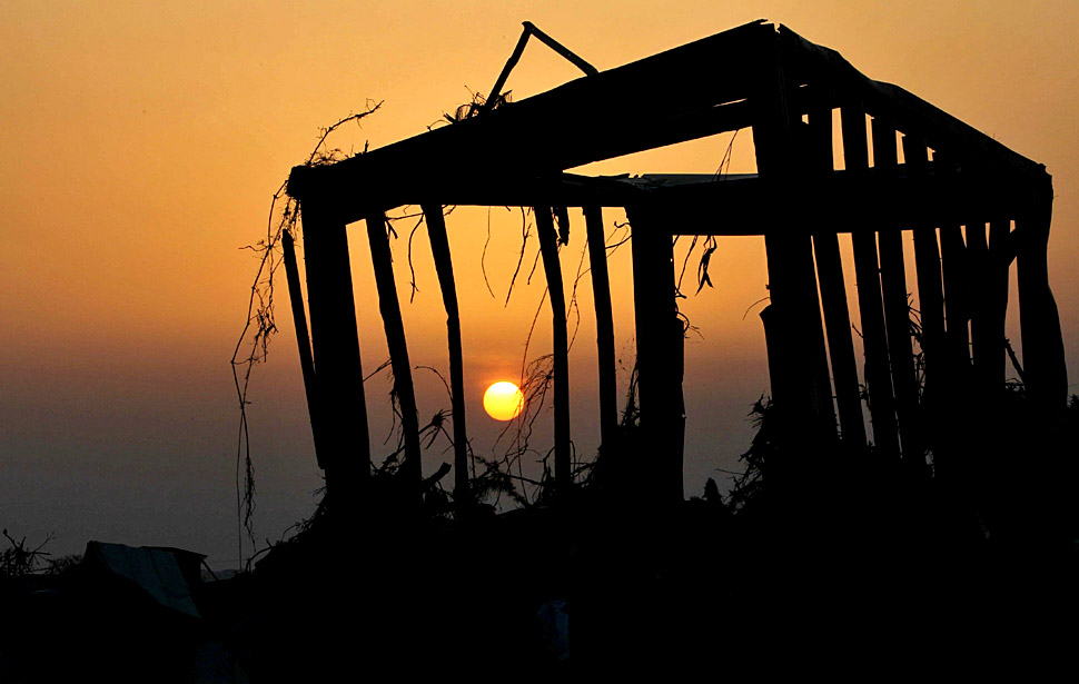 The frame of a house damaged by the earthquake and tsunami is silhouetted against the sky at sunset in Higashimatushima City, Miyagi Prefecture