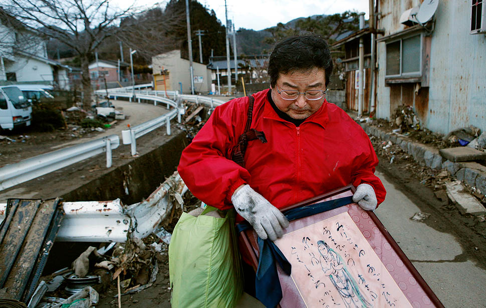 Masahiro Haaamaguchi holds a cherished artwork he recovered from his home in Kesennuma. As a welfare worker, he is unhappy that more aid is not reaching the area