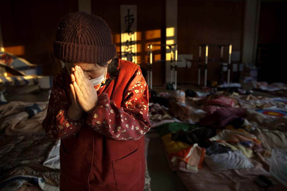 Momoko Onodera, at an evacuation center Kesennuma, prays as she talks about her husband who died in the tsunami
