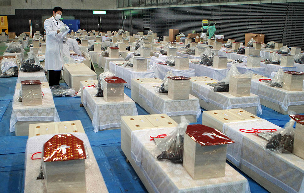 Coffins fill a hall. The official number of dead and missing after the devastating earthquake and tsunami that flattened Japan's northeast coast a week ago has topped 16,000
