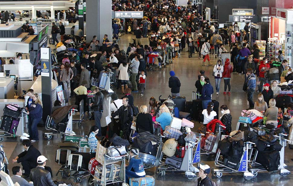 Passengers form long lines to check in for flights at Narita airport east of Tokyo