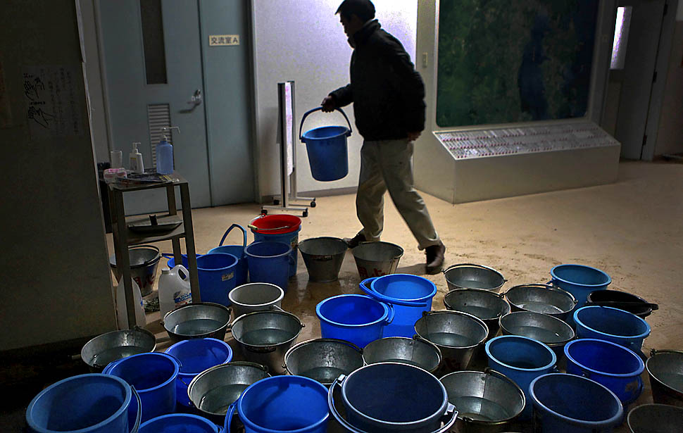 A man carries a bucket of water to flush a toilet at a city government office