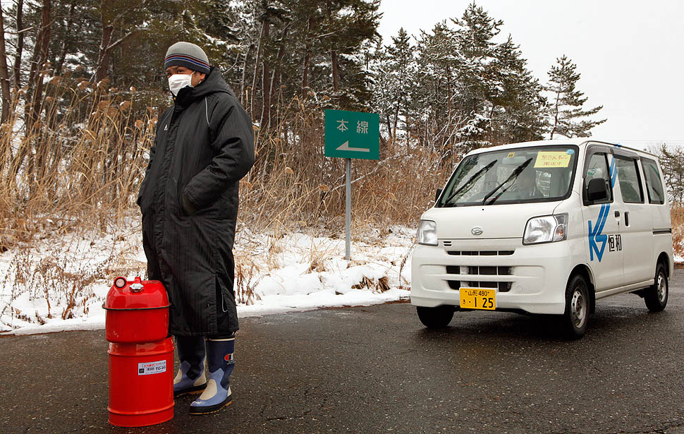 On the Tohoku Expressway between Sendai and Morioka, a man waits in line for gasoline