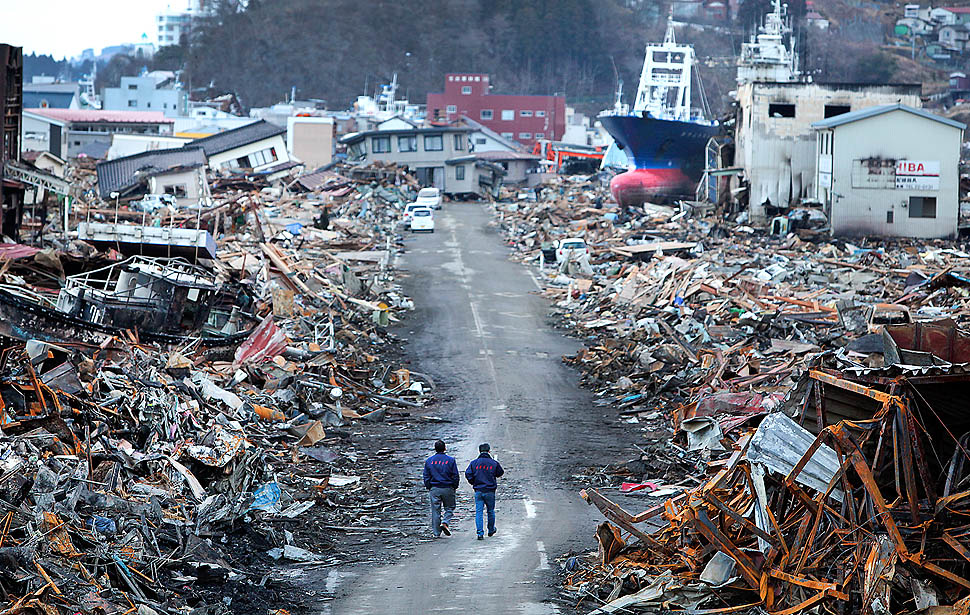Government officials walk down a recently cleared roadway where the earthquake-spawned tsunami caused a massive fuel spill and fire