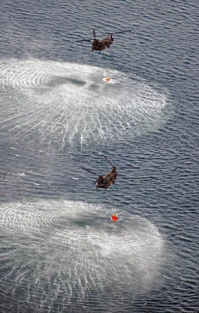 Japanese military helicopters pick up water to dump onto the stricken Fukushima nuclear powe plant in a bid to douse radioactive fuel rods