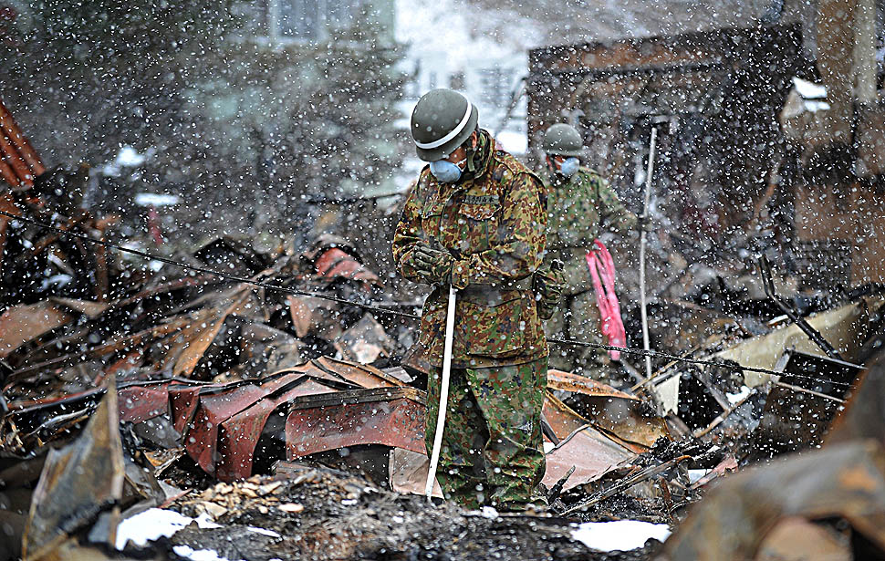 A Japanese Self Defense Force solders prays during a snowfall before removing the body of a tsunami victim