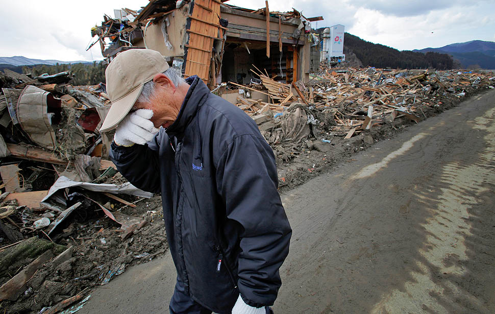 Katsuo Maiya, 73, cries in front of the rubble where his sister's home stood