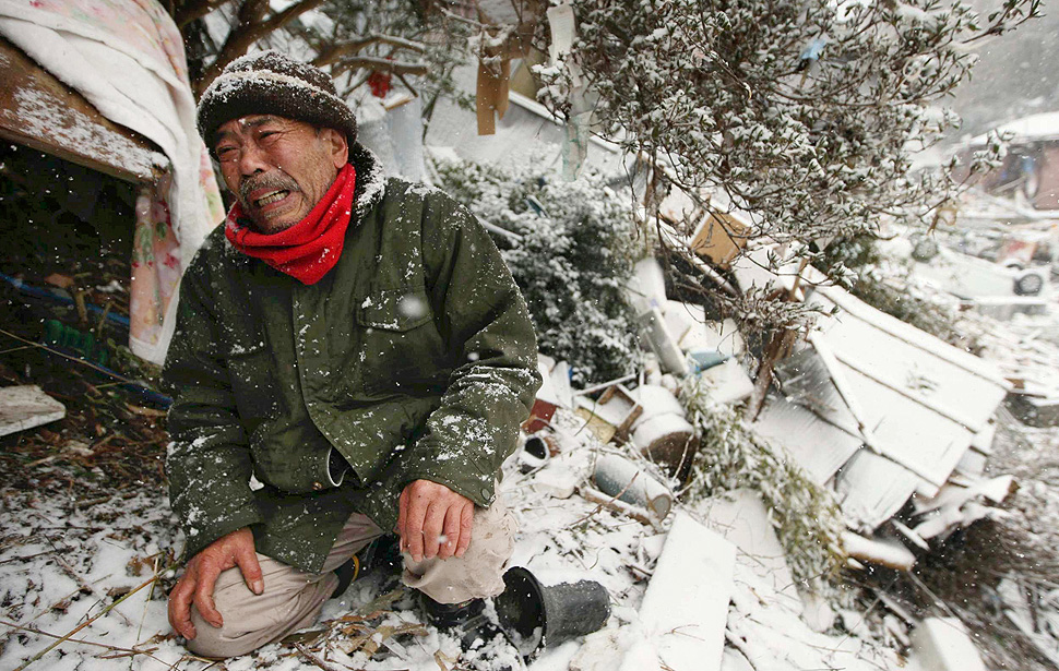 A man cries next to his destroyed house where his dead mother is still buried under rubble