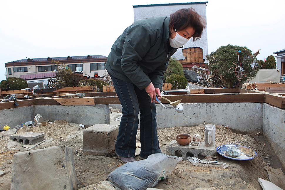 Noriko Sato, 57, collects household items from her home, which had been moved more than 100 meters by the tsunami in Yamada Town, Iwate Prefecture