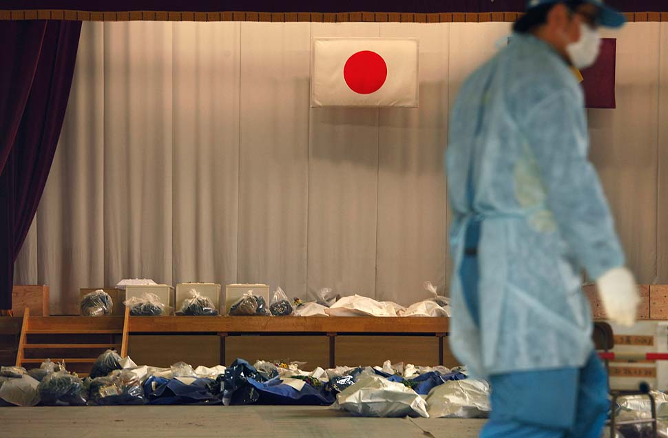 A Japanese flag hangs above the remains of tsunami victims in a temporary morgue set up in the gymnasium of the town's junior high school.