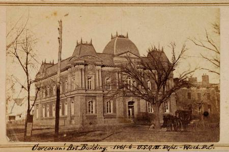 Sepia tone photograph of the Corcoran art building surrounded by trees with a small white cottage behind it