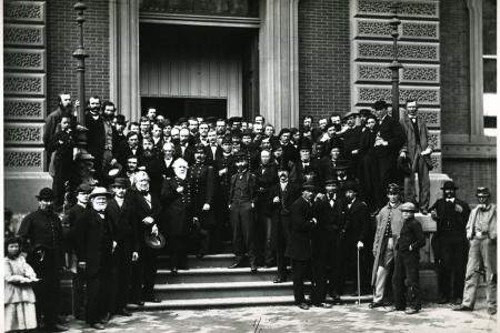 Over 60 young and old men with stern faces in suits and military regalia line the front steps of the building