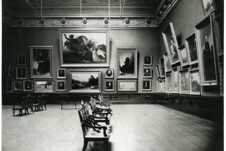 Wooden chairs face the artwork in a once ornately painted grand salon.