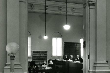 Four men in suits busily sit behind desks shuffling through papers.
