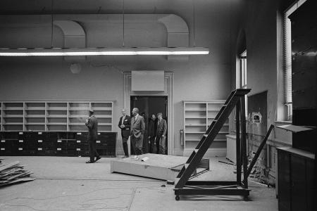 This black and white photo shows President Johnson walking through a large room in the Renwick with crumbling walls and empty bookshelves.