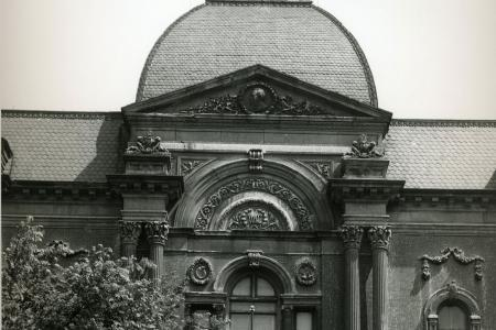 This black and white photo depicts a construction crane atop the front entrance of the Renwick.