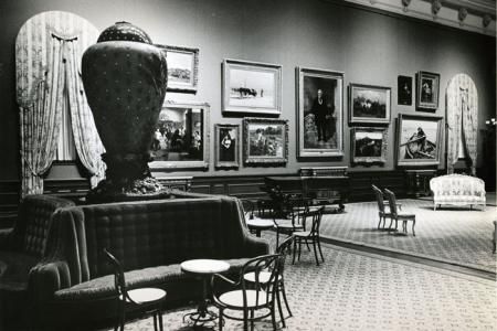 This black and white photo depicts paintings hung from floor to ceiling in this multi-story room.