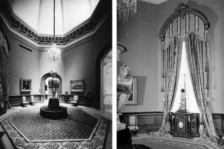 A crystal chandelier hangs from the center of the octagonal room above a large ornately decorated vase.  Lavish curtains hang from the window, adorned with eight large tassels.