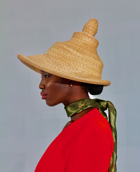 Model in profile wearing tiered woven straw hat