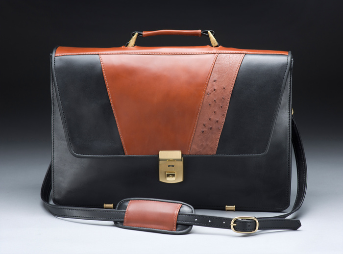 Black leather purse with a gold buckle and brown accents