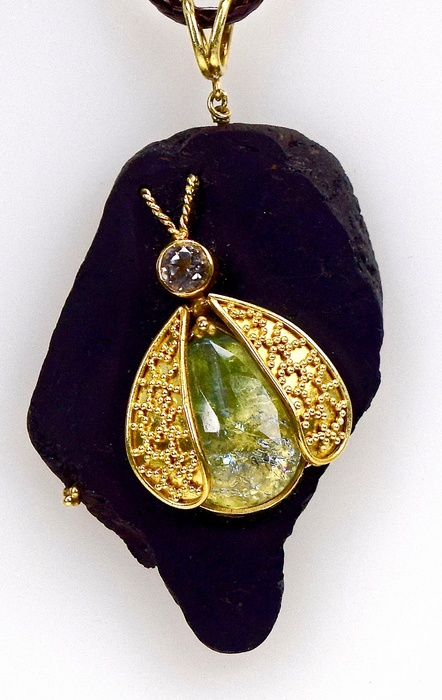 gold necklace with green teardrop shaped pendant