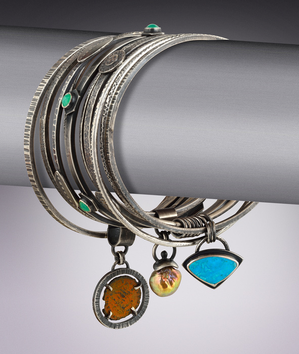A stack of bracelets with dangling pendants