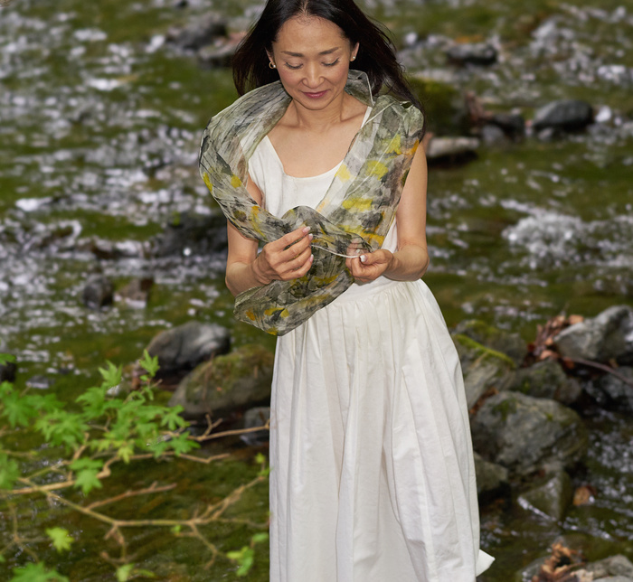 Model standing in a forest wearing dress and greenish scarft