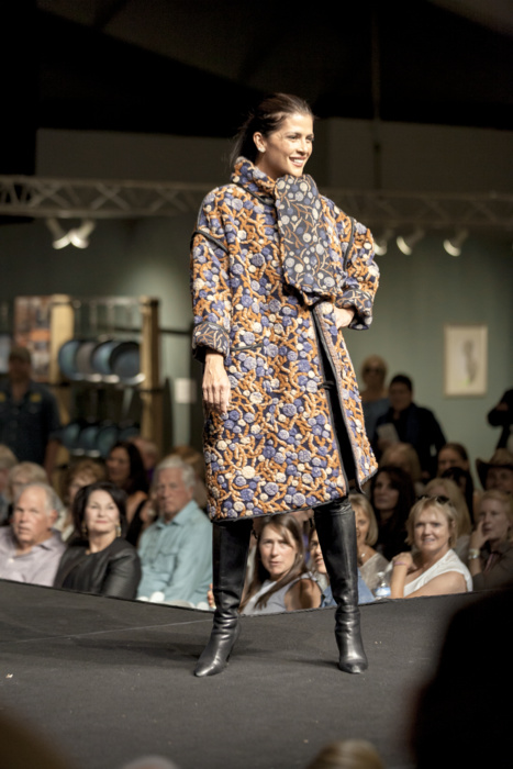 Model in orange and blue floral coat with scarf