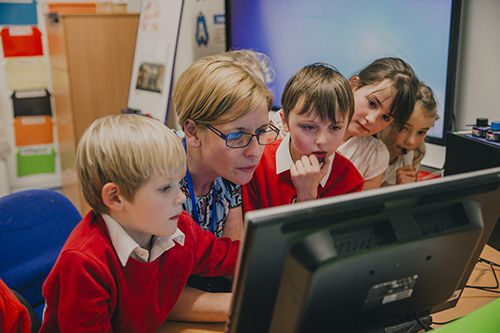 Photo of school kids and teachers looking at a computer screen