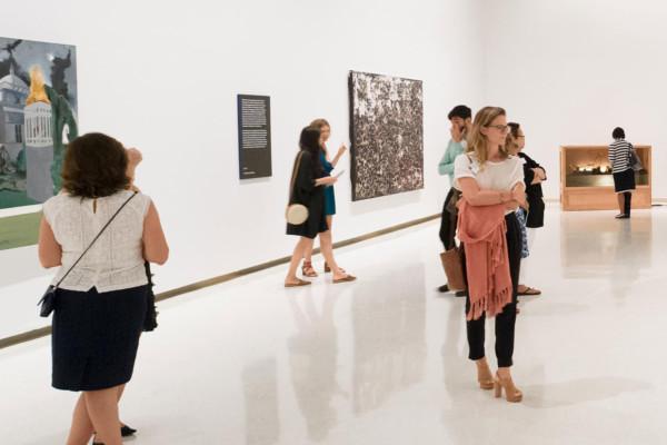 People observing and discussing artwork in a gallery.