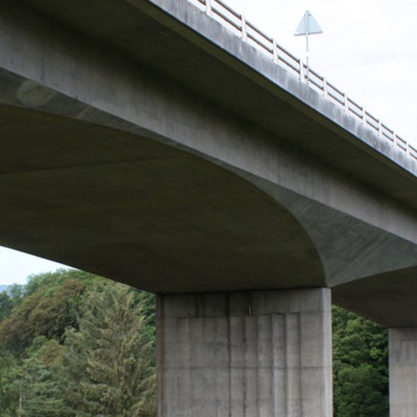 View of the underside of an expressway overpass with hills in the background