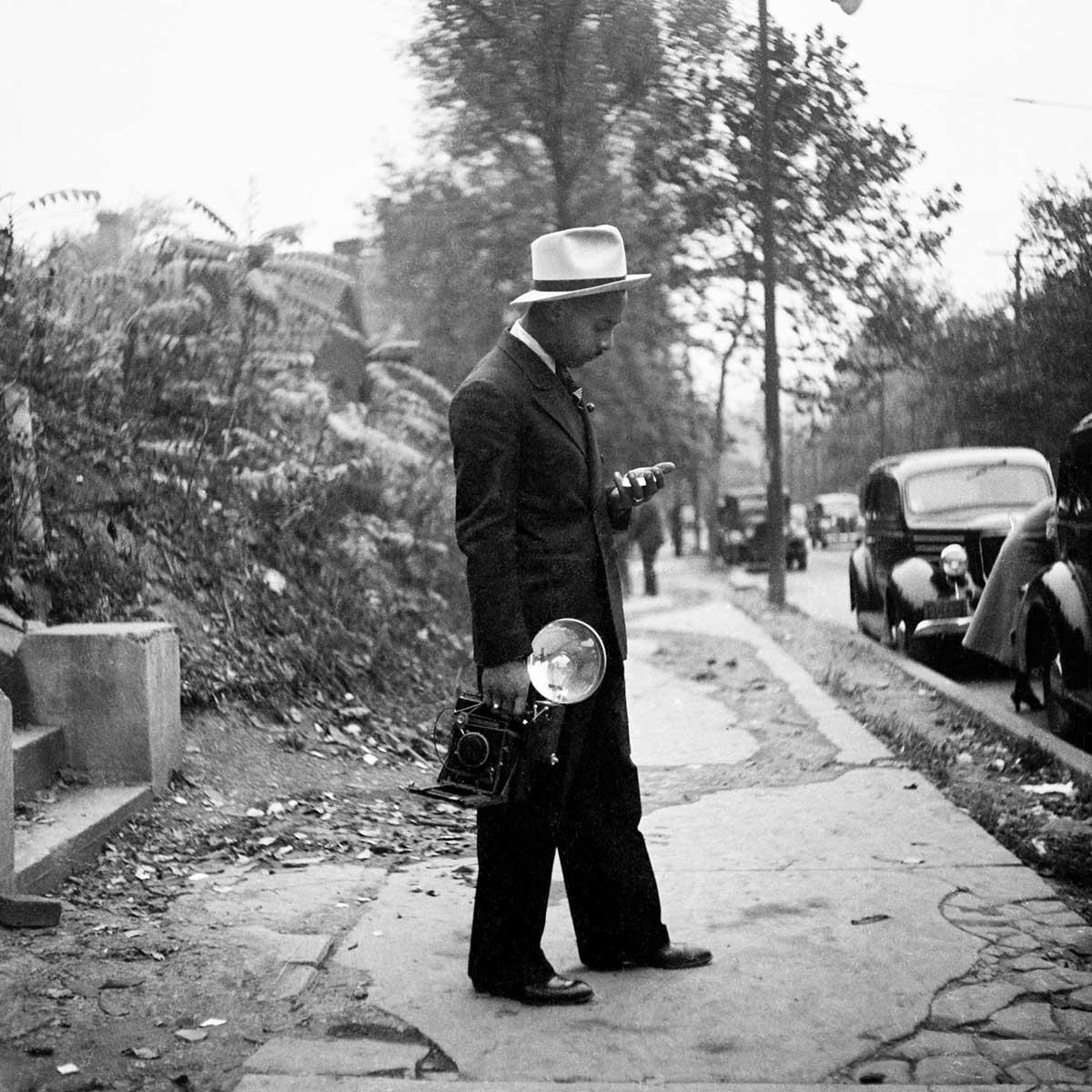 """Charles """"Teenie"""" Harris standing on sidewalk holding his camera"""
