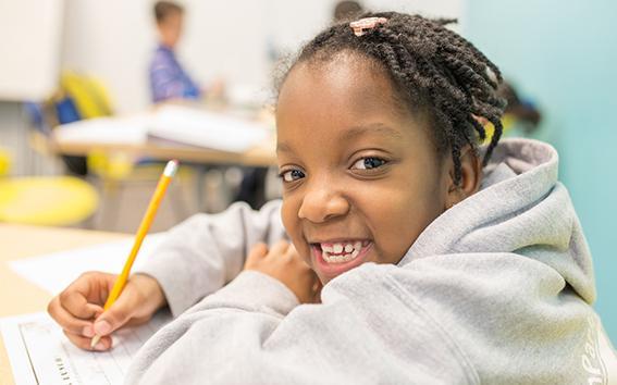 Smiling child doing school homework.