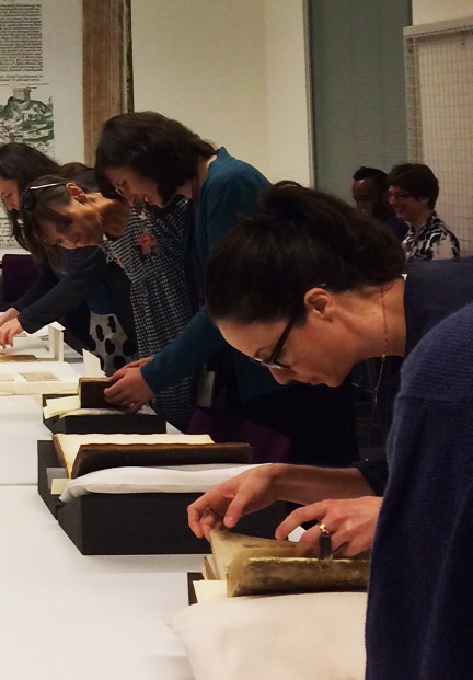 People viewing medieval manuscripts.