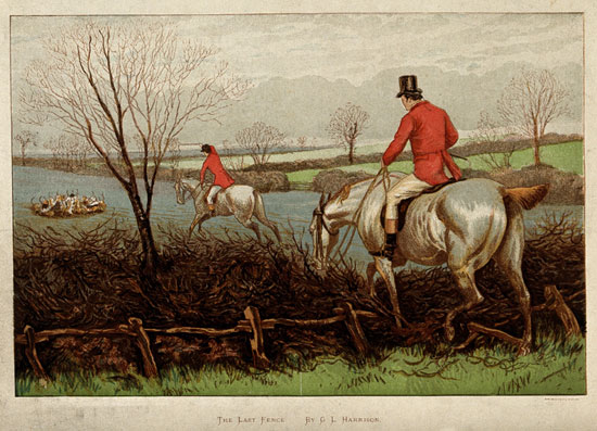 Two mounted huntsmen in red jackets guide their horses over a hedge into a field where hounds are gathered around a fox