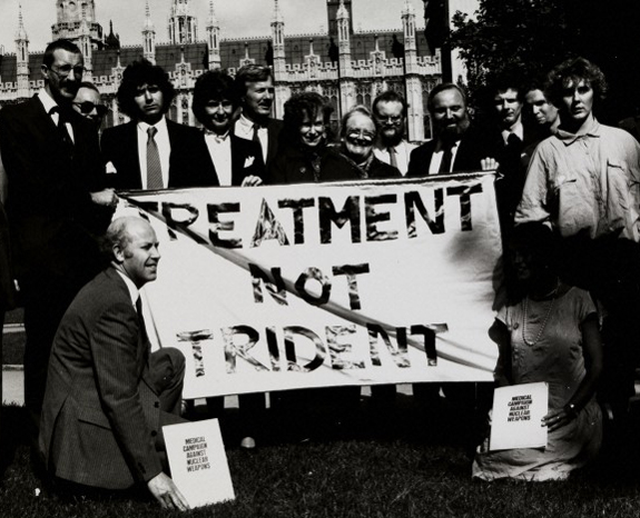L0075326 MCANW - Treatment Not Trident, 1988 Credit: Wellcome Library, London. Wellcome Images images@wellcome.ac.uk http://wellcomeimages.org MCANW - Treatment Not Trident, 1988.  Dr Stephen Farrow, Chair of MCANW. SRN Nicolas Woodward, Executor of MCANW (?). Medact was formed in 1992 as a merger between the Medical Campaign Against Nuclear Weapons (MCANW) and the Medical Association for the Prevention of War (MAPW). Photograph 1988 Medact  Published:  -  Copyrighted work available under Creative Commons Attribution only licence