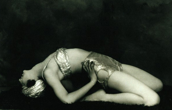 Marguerite Agniel posing leaning back wearing a revealing silver (?) two-piece costume and matching turban, on a rug, in a photographic studio. Photograph by J. de Mirjian, ca.1929. Wellcome Images reference: V0048582 .
