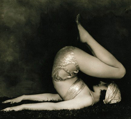 Marguerite Agniel posing with her back arched and  Marguerite Agniel posing leaning back wearing a revealing silver (?) two-piece costume and matching turban, on a rug, in a photographic studio. Photograph by J. de Mirjian, ca.1929. Wellcome Images reference: V0048583.