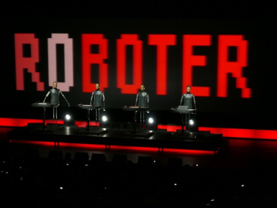 Kraftwerk - or rather, the band's robotic alter-egos - on stage in Wolfsburg, 2009 (photo by Ronald Preuß, made available under Creative Commons).