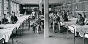 Photograph showing soldiers sitting on iron bedsteads in a hospital ward.