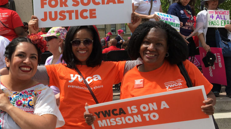 Women in YWCA tee shirts with signs reading