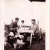 Ed, Carl and August Kerbes, accompanied by the family dogs, enjoy food and drink outside the family home near Stettler.