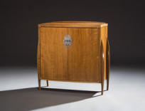 Three Twins No. 1 Description: A low, bow-front cabinet in old stock teak and teak veneers, with curved, faceted Deco-inspired legs. Engraved nickel silver escutcheon plate; interior of olive ash. Dimensions: H:31.00 x W:39.00 x D:14.00 Inches